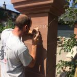 Hand carving house name into new sandstone pillars